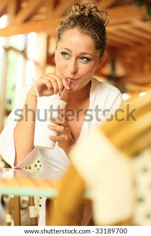 young blond woman in bathrobe drinks with a straw out of a mug