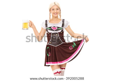 Young blond woman in Bavarian costume holding a pint of beer and looking at the camera isolated on white background