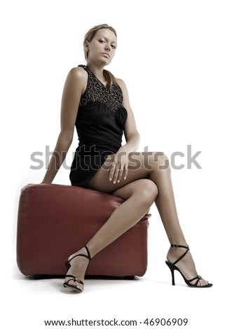 Young blond woman in black dress sitting on pouffe