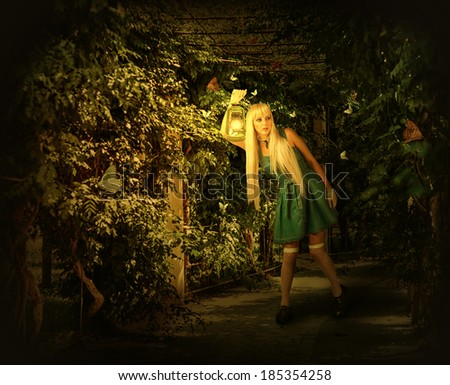 Young blond woman in dress walking on a mysterious path into an enchanted forest. She holding kerosene lamp - stock photo