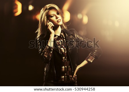 Young blond woman in leather jacket calling on mobile phone. Stylish fashion model in a subway