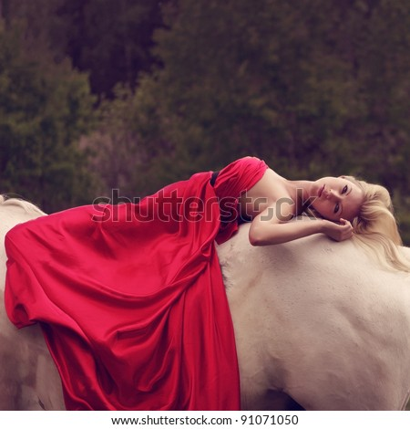 young blond woman in red lying on a horse - stock photo