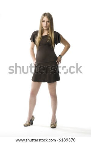 Young blond woman in short dress standing on white backdrop  with a serious look.