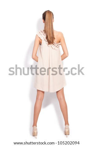 young blond woman in short elegant dress and high heel shoes , back view, full body shot, studio white - stock photo
