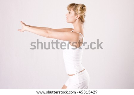 young blond woman in white sportswear makes athletic exercises - stock photo