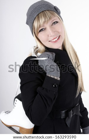Young blond woman in winter clothes with ice skates - stock photo