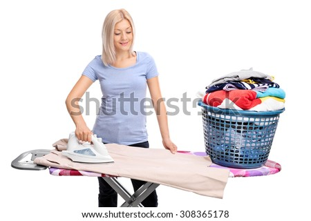 Young blond woman ironing clothes on an ironing board isolated on white background - stock photo