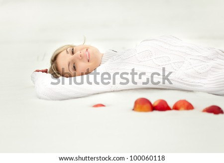 Young blond woman is lying in the snow. Some apples are near her. - stock photo