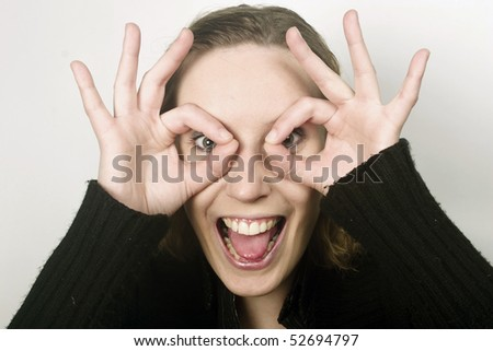 Young, blond woman is peeking thorough circles made from her fingers and showing tongue - stock photo