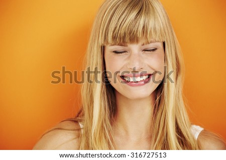 Young blond woman laughing in studio