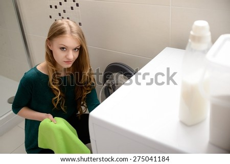 Young blond woman loading clothes into washing machine in bathroom - stock photo