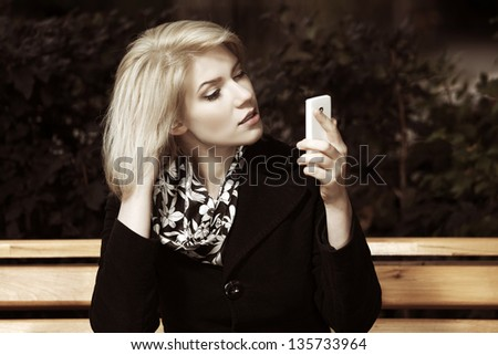 Young blond woman looking at mobile phone - stock photo
