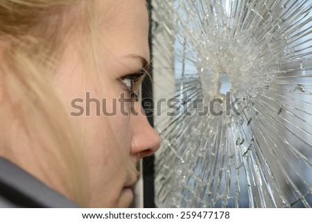 Young blond woman looking on windowpane - stock photo