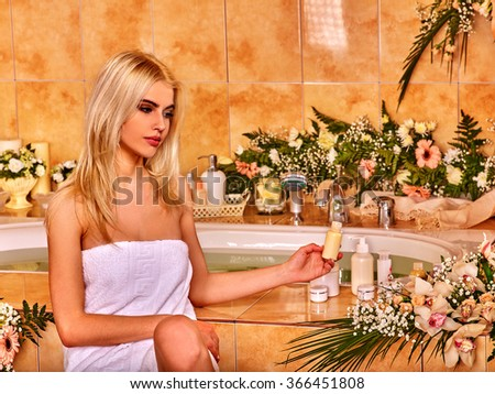 Young blond woman luxuriate at flowers water spa.  - stock photo