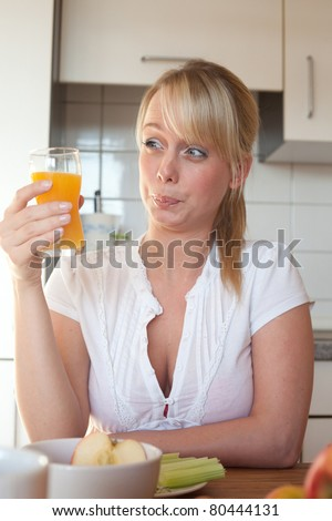 young blond woman makes a face/young blond woman with a glass of juice makes a face
