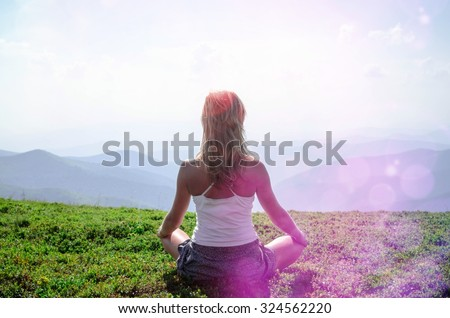 Young blond woman meditating in the beautiful mountain landscape. Carpathian mountain range and blue sky. - stock photo