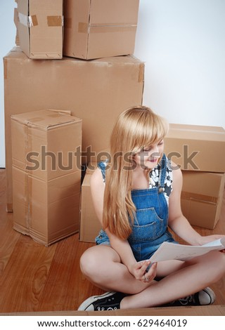 Young Blond Woman Moving Into New Apartment, Unpacked Furniture