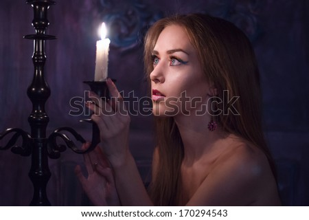 Young blond woman near the burning candles. Studio shot