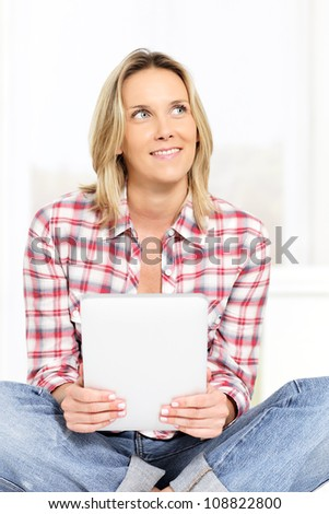 young blond woman on sofa with tablet - stock photo