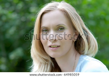 Young blond woman portrait at the green bokeh background