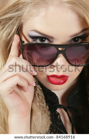 Young blond woman portrait looking over dark sunglasses - stock photo