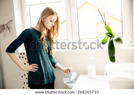 Young blond woman pouring washing powder into the washing machine - stock photo