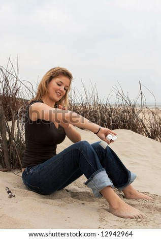 Young blond woman putting on suntan lotion