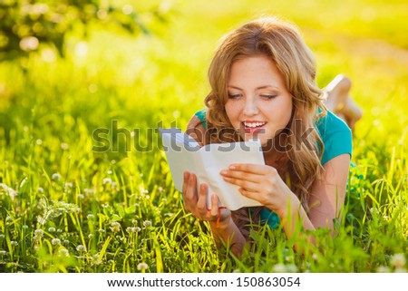 young blond woman reading a book lying on the grass in the shade - stock photo