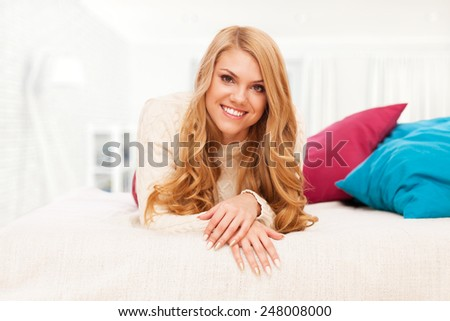 Young blond woman relaxing in bed - stock photo