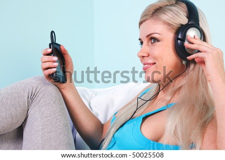 Young blond woman sat in an armchair listening to music on her mp3 player through headphones