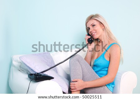 Young blond woman sat in an armchair talking on the telephone