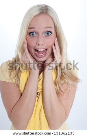 young blond woman shows a gesture of surprise/young blond astonished woman/woman is surprised