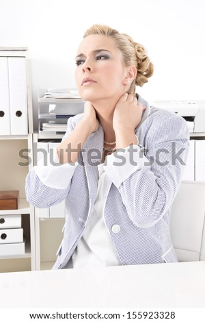 Young blond woman sitting in office with aching neck - stock photo
