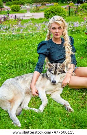 Young blond woman strokes Husky dog sitting on grass in summer park.