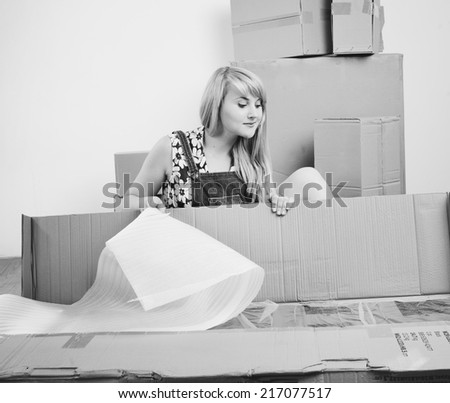 Young blond woman unpacking box of new furniture.