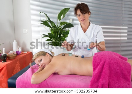Young blond woman waiting for massage with crystals