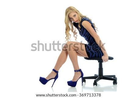 Young blond woman wearing a blue dress and high heels isolated on a white background - stock photo