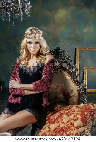 young blond woman wearing crown in fairy luxury interior with empty antique frames total wealth, magic rich concept - stock photo