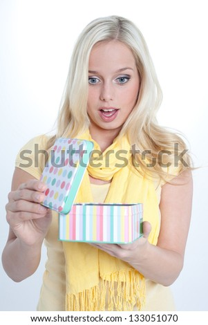 young blond woman with a gift box is surprised|amazed woman with a gift box/woman with a gift pack
