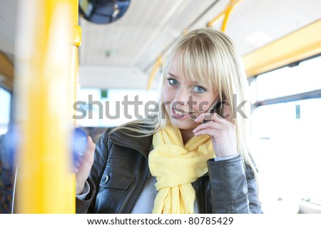 young blond woman with a smart-phone inside a bus/young blond woman with a smartphone inside a bus
