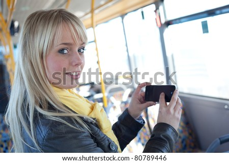young blond woman with a smartphone inside a bus/young blond woman with a smartphone in her hands inside a bus