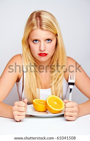 young blond woman with an orange on a plate with silverware - stock photo