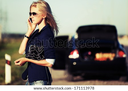 Young blond woman with broken car calling on the cell phone - stock photo