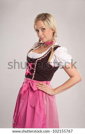 young blond woman with dirndl dress blows someone a kiss/young blond woman dressed with dirndl for oktoberfest/young blond woman with dirndl costume