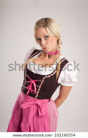 young blond woman with dirndl dress makes a kiss-mouth/woman with dirndl makes a kiss-mouth/woman with dirndl - stock photo