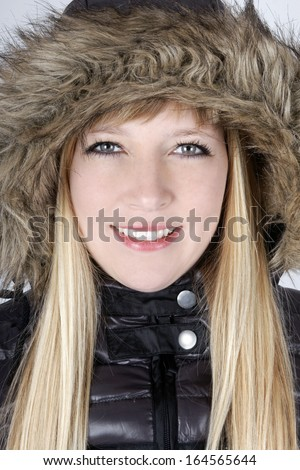 Young blond woman with furry hood in winter - stock photo