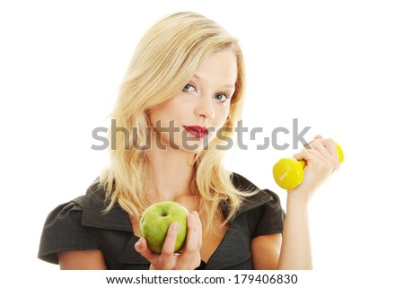Young blond woman with green apple and yellow dumbbell - healthy living concept  - stock photo