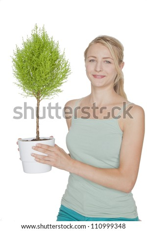young blond woman with green  bonsai tree - stock photo