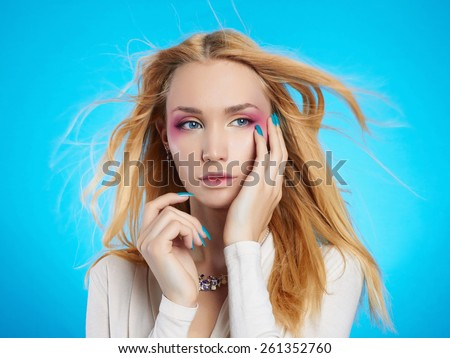 Young Blond woman with manicure.Beautiful girl model with make-up.Blue Background - stock photo