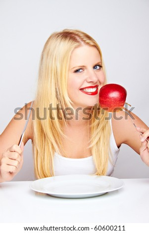 young blond woman with red apple on a fork - stock photo